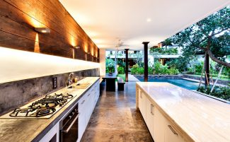 Outdoor Kitchen With A Stove An Countertop Next To Garden